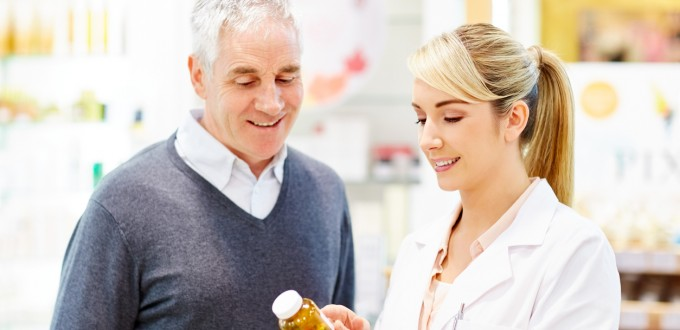Smiling pharmacist explaining prescription to customer. Beautiful professional is discussing over medicines with man. Both are in brightly lit drug store.